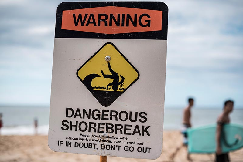 Safety officials post signs to alert beachgoers of hazardous conditions such as dangerous shorebreak. Valeria Venezia/Shutterstock.com