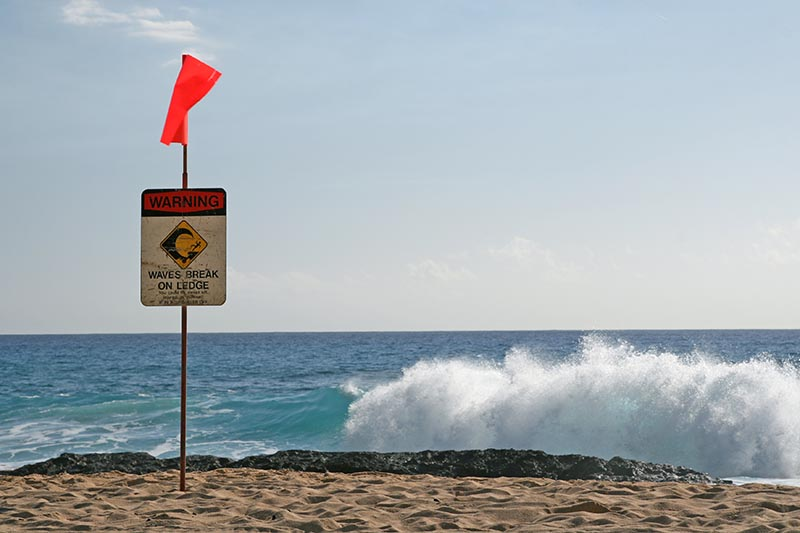 A sign warns beachgoers to be cautious of waves breaking on the ledge. Henry William Fu/Shutterstock.com