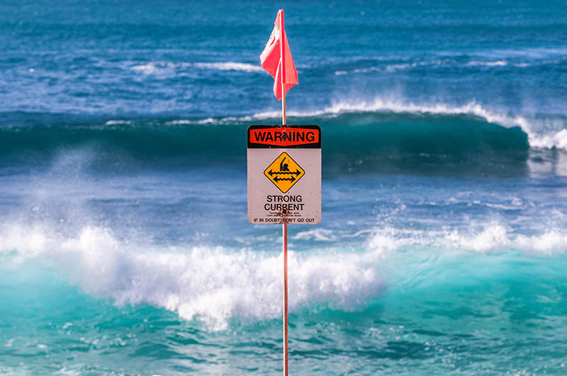A strong current sign warns beachgoers of dangerous conditions. Shamana/Iren Key/Shutterstock.com